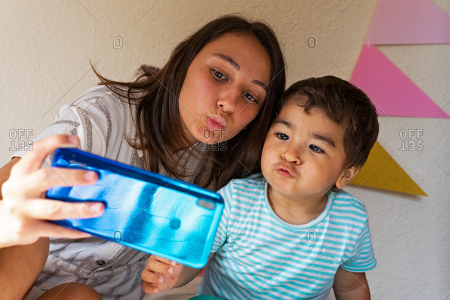 Delighted young woman and mixed race toddler smiling and taking selfie against wall with flags at home