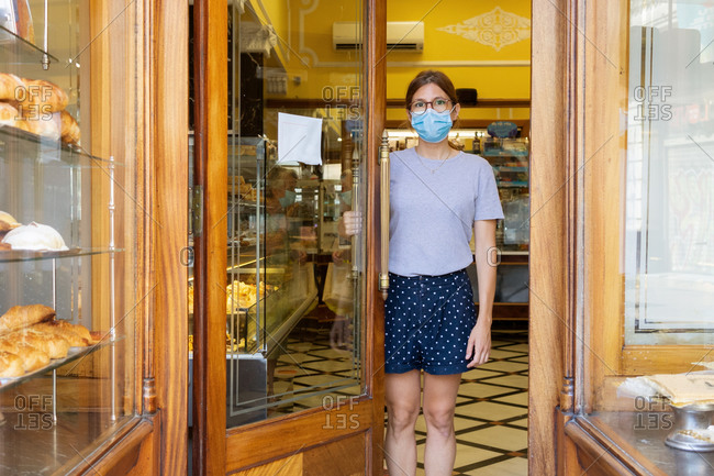 Young female seller in medical mask standing at doorway of cozy bakehouse and looking at camera