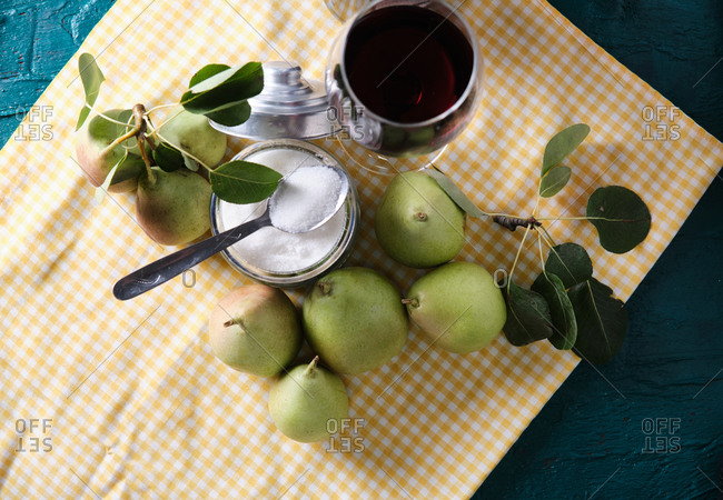 Top view of ripe pears and sugar arranged on table with glass of red wine in kitchen