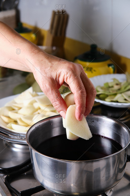 Unrecognizable female cook adding slices of pears in saucepan with red wine while preparing sweet poached fruits at home