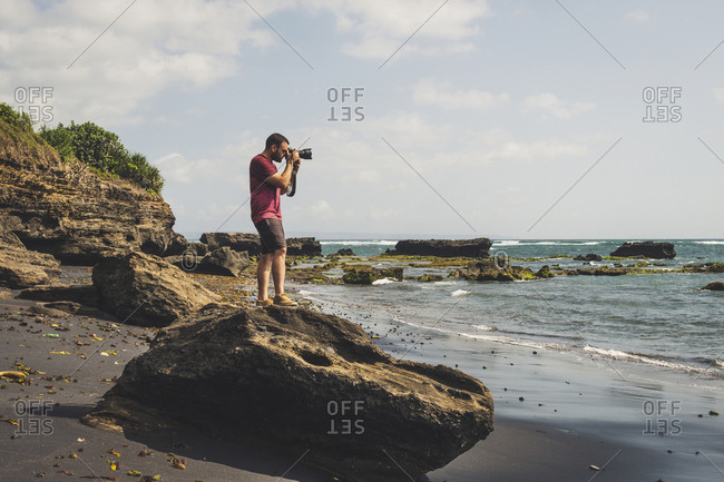 Side view of traveling man with professional photo camera standing on rock on beach and taking picture of amazing seascape in summer