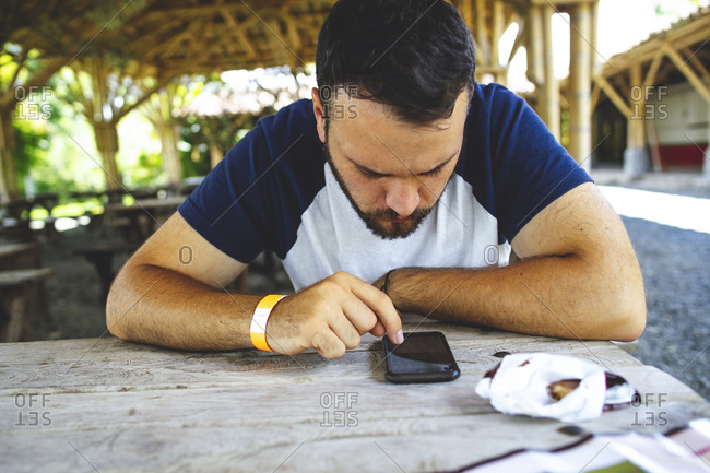 Busy male sitting at wooden table in outdoors cafe and browsing cellphone while resting in city in summer