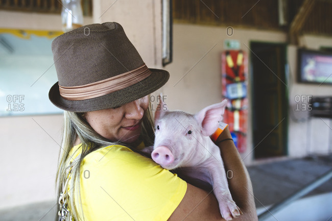 Smiling female standing in city near building and hugging adorable little pink pig