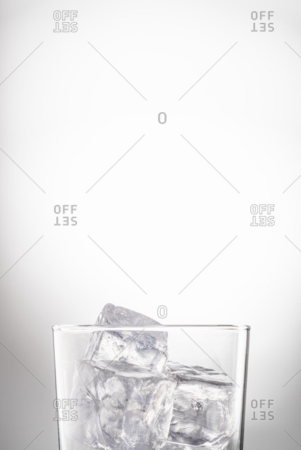 Crystal glass with water and ice cubes placed in studio on white background