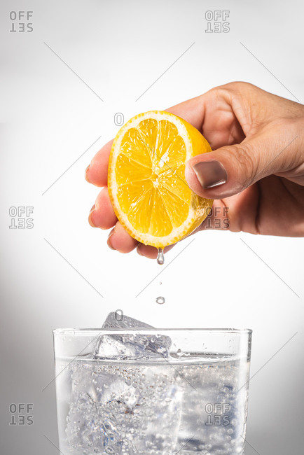 Crop female squeezing lemon juice in glass of water with ice cubes while preparing detox drink