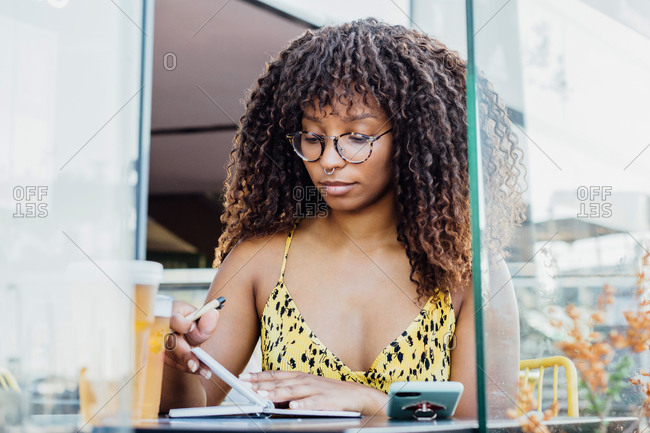 Black self employed woman sitting at table in cafe and working remotely while writing in notepad