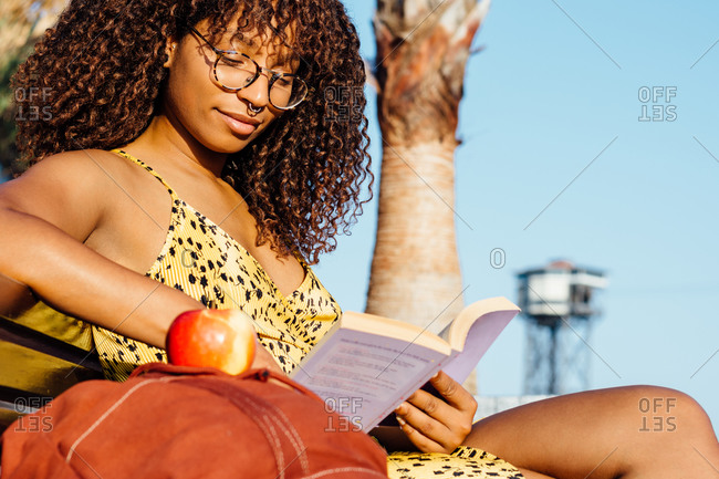 Low angle of content black female in eyeglasses sitting on bench in garden in summer and reading interesting book during weekend