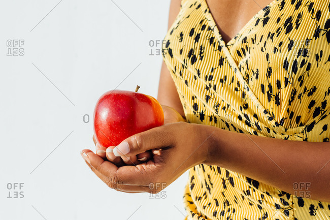 Unrecognizable ethnic female standing with ripe red apple on white background in studio
