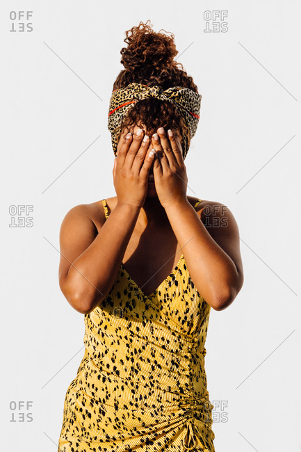 Smiling African American female wearing summer dress and trendy headband standing near wall in city and covering face while looking at camera