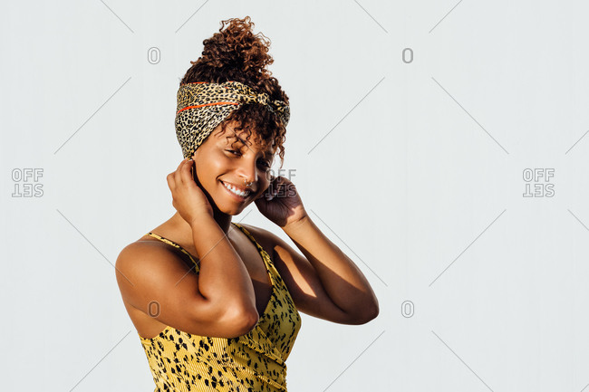 Smiling African American female wearing summer dress and trendy headband standing near wall in city and touching head while looking at camera