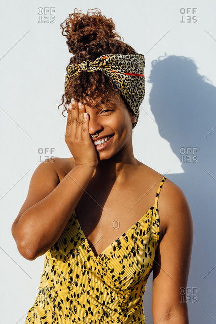 Smiling African American female wearing summer dress and trendy headband standing near wall in city and touching face while looking at camera