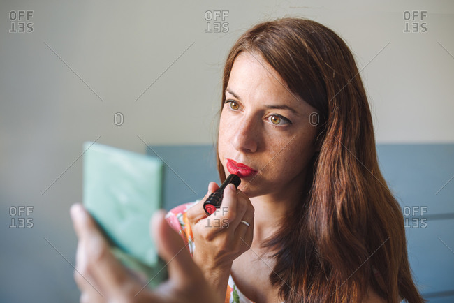 Charming young long haired female in casual clothes with small mirror in hand applying lipstick while preparing to go out