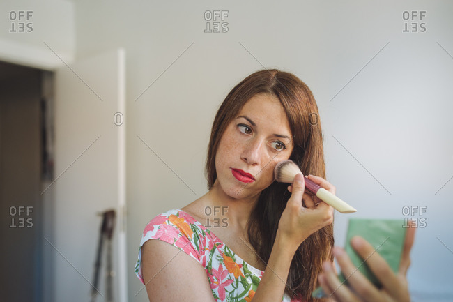 Young female in casual clothes holding mirror and applying blush with makeup brush during beauty procedure at home