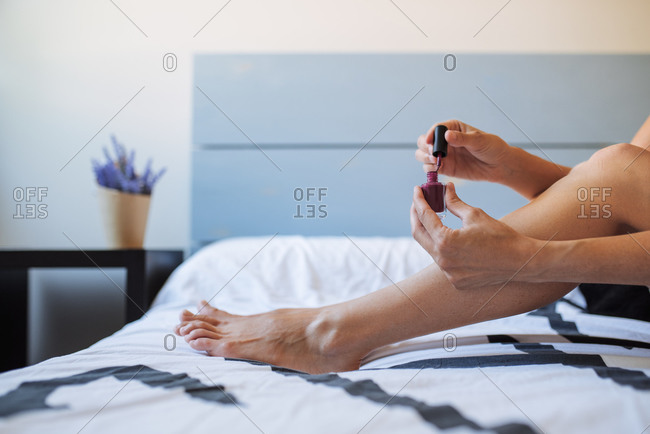Side view of crop anonymous female sitting on bed and painting nails on toes with bright nail polish during beauty session at home