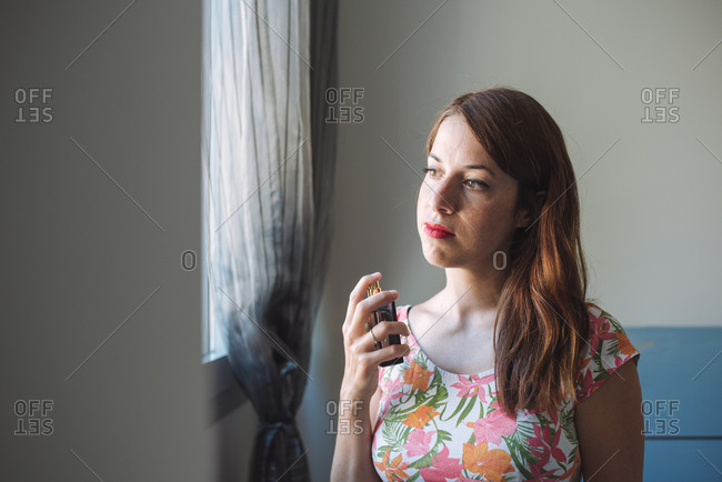 Charming young pensive female in casual outfit with soft makeup spraying perfume on neck during beauty time at home
