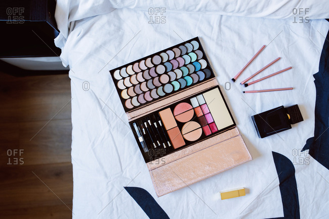 Top view of multicolored cosmetic palette with eyeshadows and rouge placed with various brushes and perfume bottle on white bed in feminine bedroom