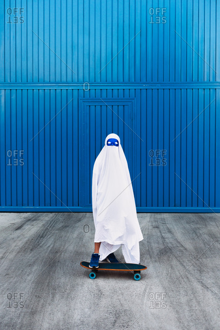Unrecognizable child wearing mask and white ghost costume standing on skateboard in city during Halloween and looking at camera