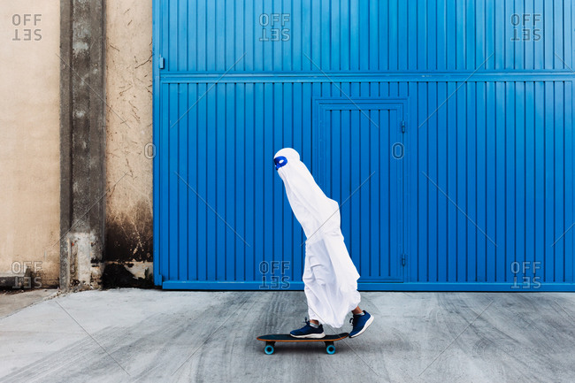 Unrecognizable child wearing mask and white ghost costume standing on skateboard in city during Halloween