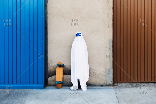 Unrecognizable child wearing mask and white ghost costume standing near skateboard in city during Halloween and looking at camera