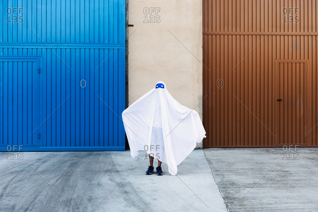 Faceless child in white ghost costume frightening with outstretched arms while standing in city during Halloween