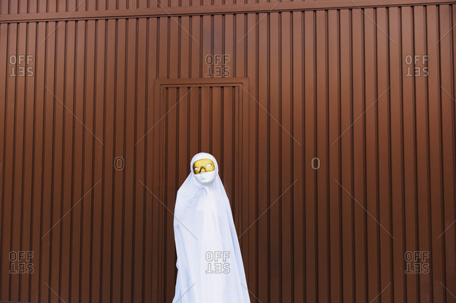 Unrecognizable kid wearing masquerade mask and ghost costume standing in city during Halloween and looking at camera