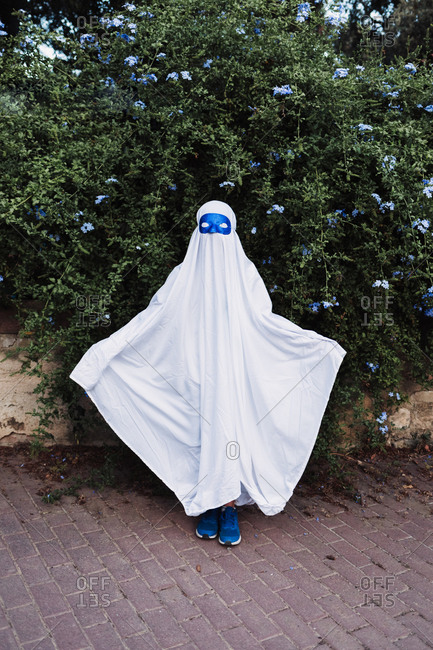 Faceless creepy child in ghost costume standing in park during Halloween on overcast day
