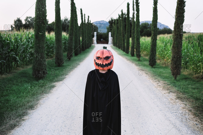 Anonymous person wearing spooky Halloween pumpkin mask and black cloak standing on sandy road