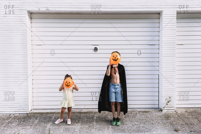 Boy and girl covering faces with balloons in shape of scary pumpkin while standing together on street during daytime