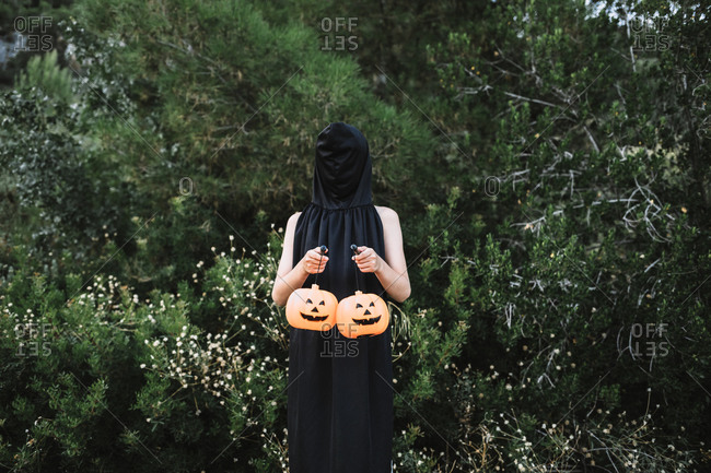 Faceless person covering face with black cape and standing with lanterns in shape of pumpkins in garden