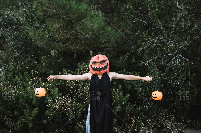 Faceless person covering face with black cape and standing with outstretch arms holding lanterns in shape of pumpkins in garden