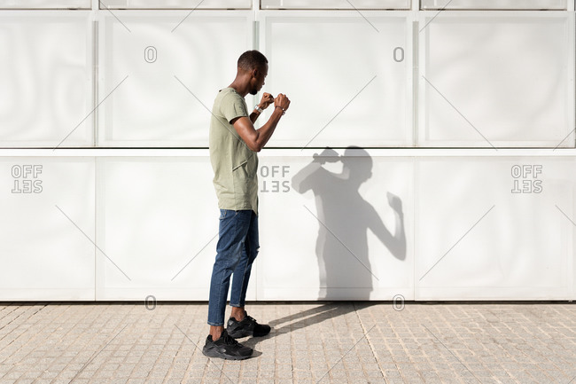 Side view of African American male standing in city in fighting position and battling with shadow on sunny day