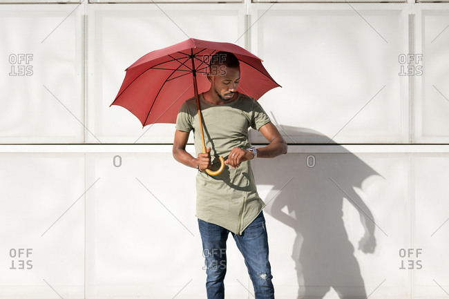 Serious African American male standing under umbrella on street on sunny day and checking time on wristwatch