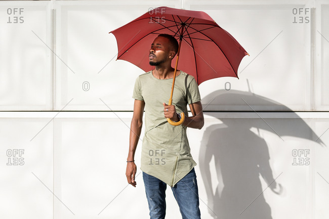 Tranquil black male standing under umbrella in city and enjoying sunny weather in summer with closed eyes