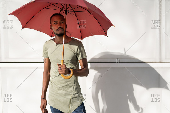 Tranquil black male standing under umbrella in city looking away and enjoying sunny weather in summer