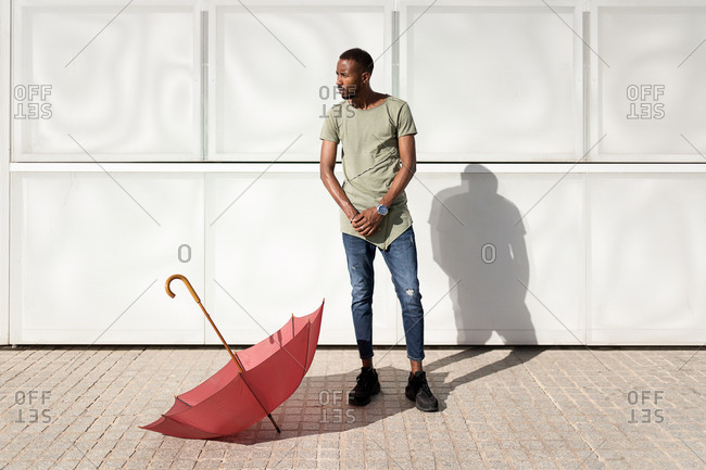 Tranquil black male standing next to umbrella on the floor in city looking away and enjoying sunny weather in summer