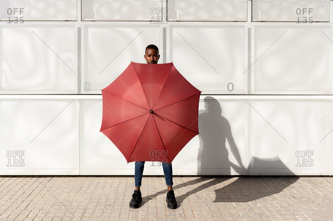 Black male standing on sidewalk in city and covering body with umbrella while looking at camera