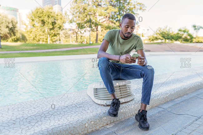 Pensive African American male sitting on border near fountain in city and surfing Internet on smartphone while chilling during
