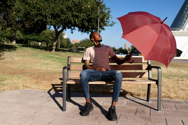 Peaceful African American male with closed eyes sitting under umbrella on wooden bench in park and enjoying weather on sunny day in summer