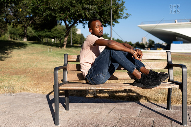 Side view of relaxed African American male sitting on bench in urban park and embracing knees while looking away