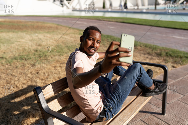 Side view of relaxed African American male sitting on bench in urban park and taking a selfie with his phone
