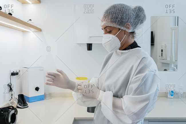 Side view of young female medical worker in white uniform and mask putting on latex gloves while preparing for treatment in modern clinic
