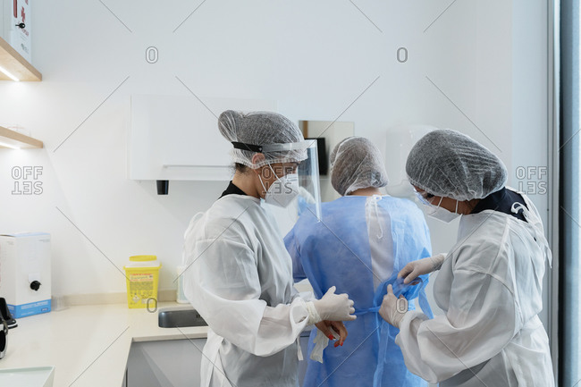 Female medical workers in protective masks and face shields helping each other to get dressed while preparing for medical procedure in hospital