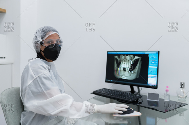 Side view of female medical specialist in protective mask and goggles with latex gloves working with scan image on computer monitor in modern clinic