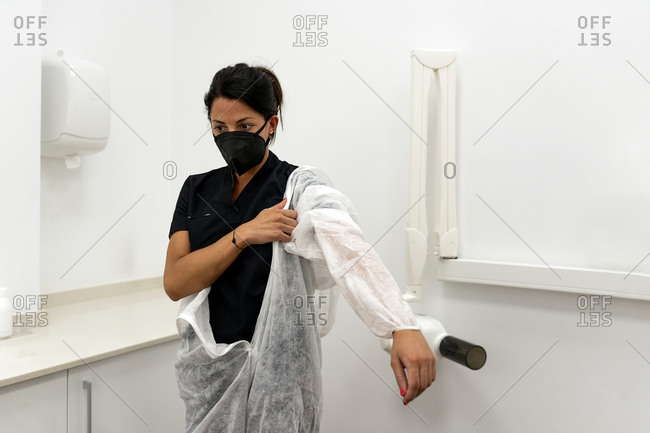 Female medical specialist putting on protective suit with face mask while preparing for work during coronavirus pandemic