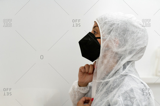 Side view of female medical specialist putting on protective suit with face mask and protective cap while preparing for work during coronavirus pandemic