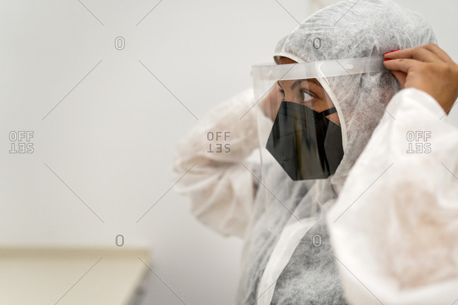 Female medical specialist putting on protective suit with face mask and protective cap while preparing for work during coronavirus pandemic