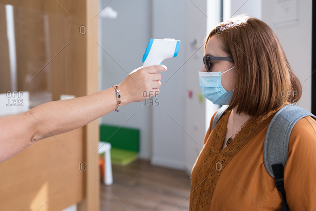 Side view of anonymous specialist with digital thermometer gun measuring temperature of female visitor in protective mask before entering clinic