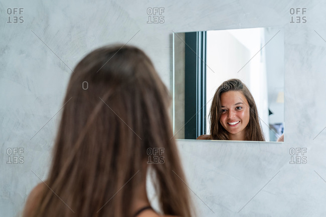 Back view of smiling female standing in modern bathroom and looking in mirror while enjoying morning