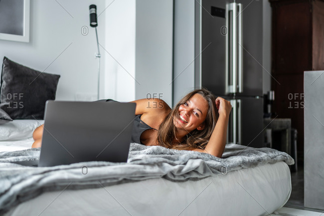 Delighted female in sleepwear lying looking at camera on cozy bed at home and typing on netbook in morning while chatting on social media