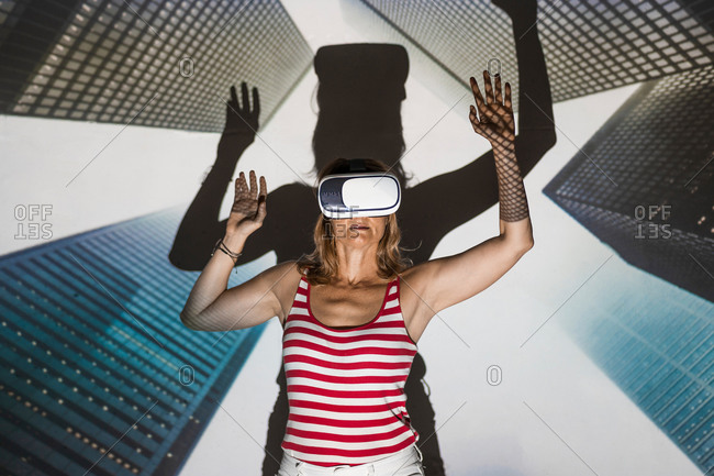 Unrecognizable female in casual wear and VR headset standing with arms raised against contemporary skyscrapers inside virtual city